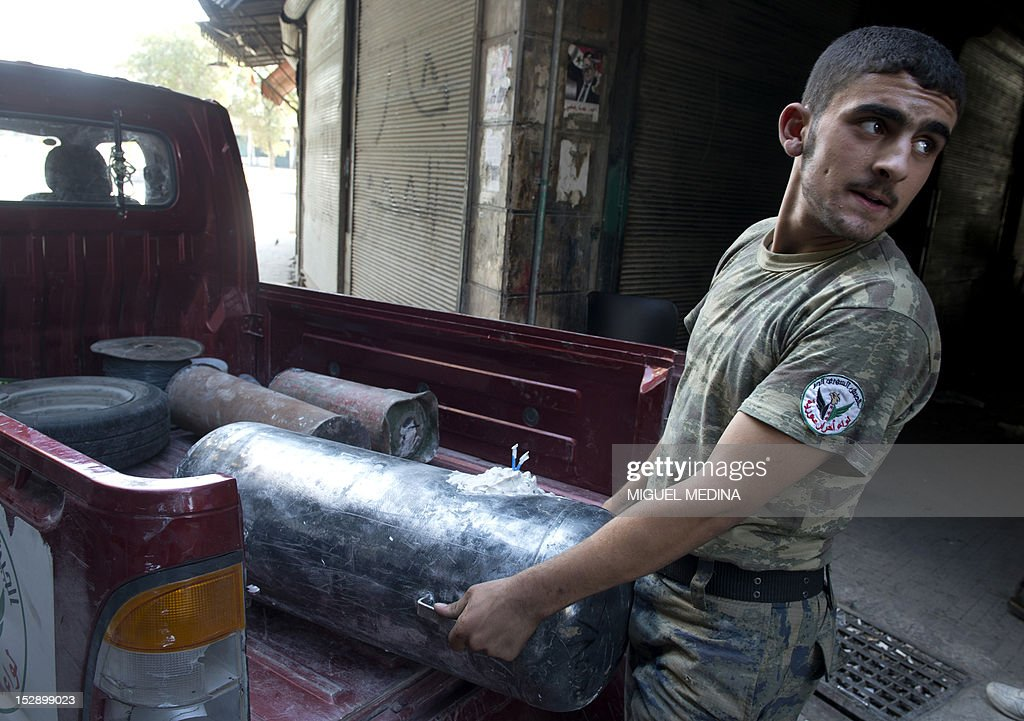 A Syrian rebel fighter unloads an Improvised Explosive Device (IED) from a pick up during fighting with government troops in the old city of Aleppo on September 28, 2012. Syrian rebels advanced on several fronts in their campaign to seize Aleppo, but without a significant breakthrough after hours of fierce fighting, commanders in the northern city told AFP. AFP PHOTO/MIGUEL MEDINA