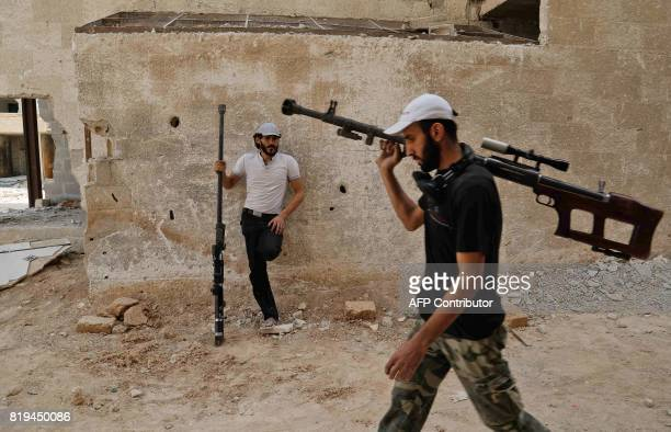 TOPSHOT Syrian rebel fighters from the Faylaq alRahman brigade carry their homemade 127mm sniper rifle in Ain Tarma in the eastern Ghouta area a...