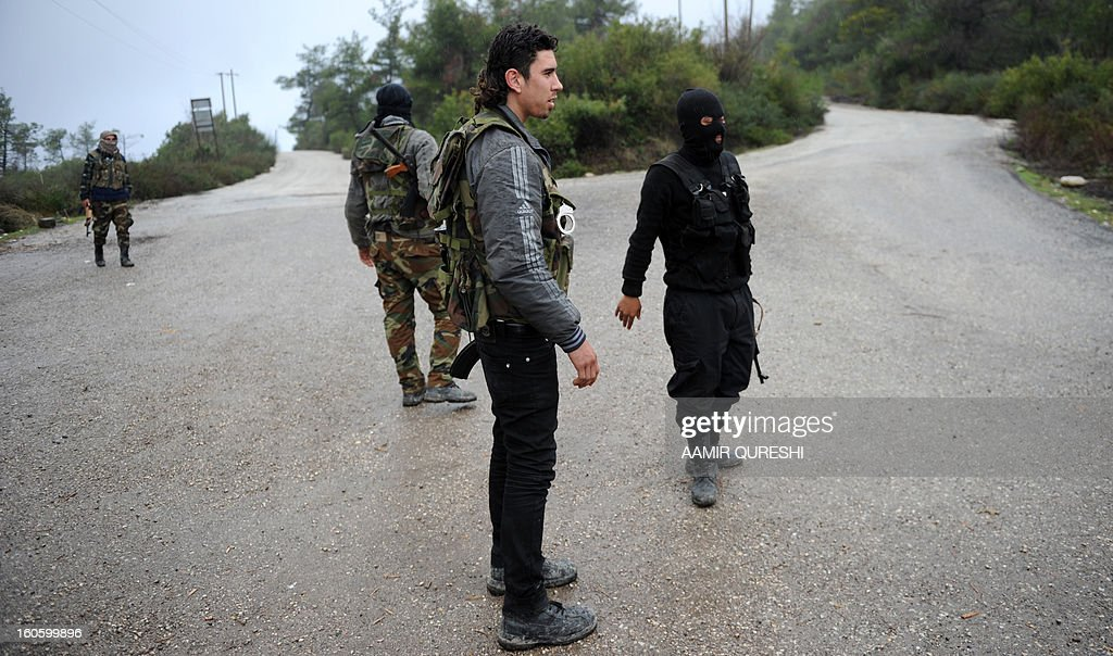 Syrian rebel fighters gather at security checkpoint in Syria's northern Latakia province on February 3, 2013. At at least 15 people, including five children and a woman, were killed in a missile attack by the army on a rebel-held area of the northern city of Aleppo, according to the Syrian Observatory for Human Rights.