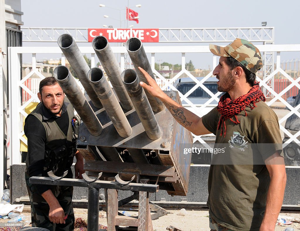 Syrian rebel fighters look at a multi-rocket launcher in Tal Abyadh, a Syrian town close to the Turkish border (behind) on October 4, 2012. Turkey hammered Syrian targets in reprisal for deadly cross-border fire that sent tensions soaring in the tinder-box region, prompting international calls for restraint.