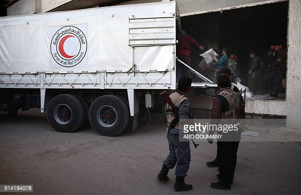 Syrian rebel fighters stand guard as sacs of aid are unloaded from a Syrian Arab Red Crescent truck in Hammuriya in the eastern Ghouta region a rebel...