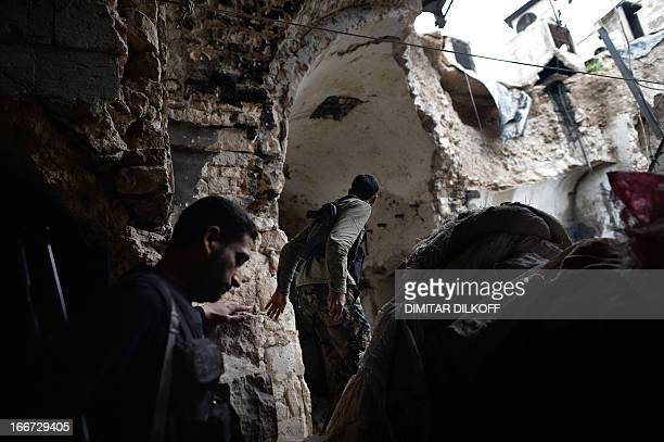 Syrian rebel fighters walk in a damaged section of the Umayyad Mosque complex in the old part of Syria's northern city of Aleppo on April 16 2013...