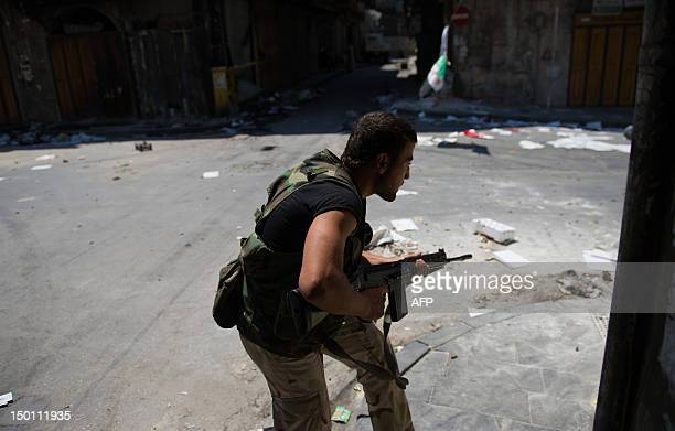 A Syrian rebel from the Free Syrian Army runs into position to fire his rifle down a street towards government snipers in the Bab AlNasr district of...