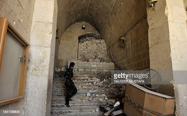 A Syrian rebel inspects damages at the Umayyad Mosque in the old city of Aleppo hours before the Syrian army retook control of the complex on October...