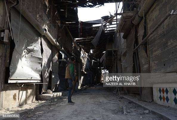 A Syrian rebel inspects the damage in the northwestern border town of alBab on February 24 2017 after Turkishbacked rebels announced the recapture of...