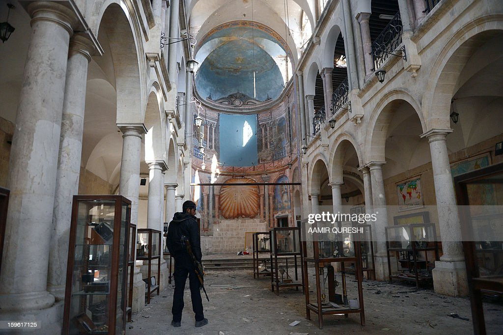A Syrian rebel looks at damaged display cases inside a former church turned into a film museum which was shelleld by government forces in Aleppo's old city on January 17, 2013. Rebels trying to break a months-long deadlock in their battle for Syria's second city Aleppo say they are cutting supply routes ahead of simultaneous assaults on regime bases.