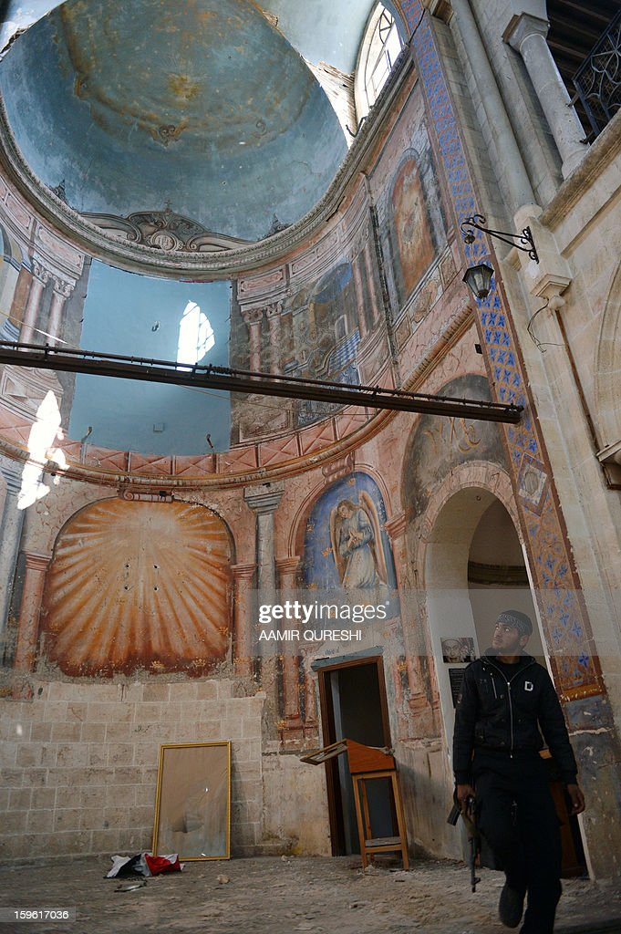 A Syrian rebel looks up inside a former church turned into a film museum which was shelleld by government forces in Aleppo's old city on January 17, 2013. Rebels trying to break a months-long deadlock in their battle for Syria's second city Aleppo say they are cutting supply routes ahead of simultaneous assaults on regime bases.