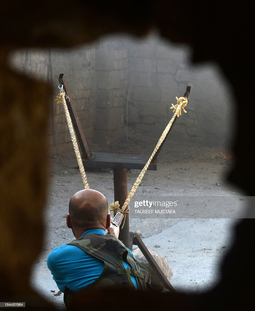 Syrian rebel readies to fire a bomb using a homemade slingshot in the northern city of Aleppo on October 16, 2012. Lightly-armed Syrian rebels who face the warplanes, artillery and tanks of loyalists have turned to making their own weapons, even rigging a video game controller to fire mortar rounds.