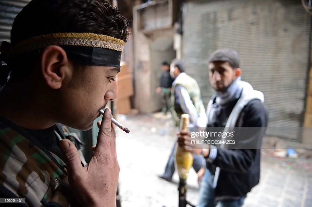 A Syrian rebel smokes a cigarette as his comrade stands guard with a Rocket Propelled Grenade (RPG) in a street in the old city of Aleppo, on November 12, 2012. Syrian troops pounded rebel lines near Damascus and in the northern city of Aleppo, while fighting raged around the northeast town of Ras al-Ain on the border with Turkey, the Syrian Observatory for Human Rights said.