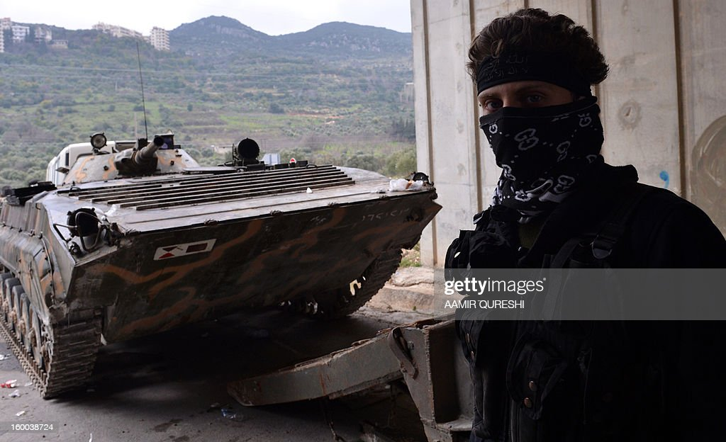 A Syrian rebel stands next to an armoured vehicle under a bridge during shelling by regime forces in the northwestern Syrian town of Jisr al-Shughur on January 25, 2013. More than 60,000 people have been killed in violence across Syria since an anti-regime revolt morphed into an armed insurgency after the regime of President Bashar al-Assad launched a brutal crackdown on dissent. AFP PHOTO/AAMIR QURESHI