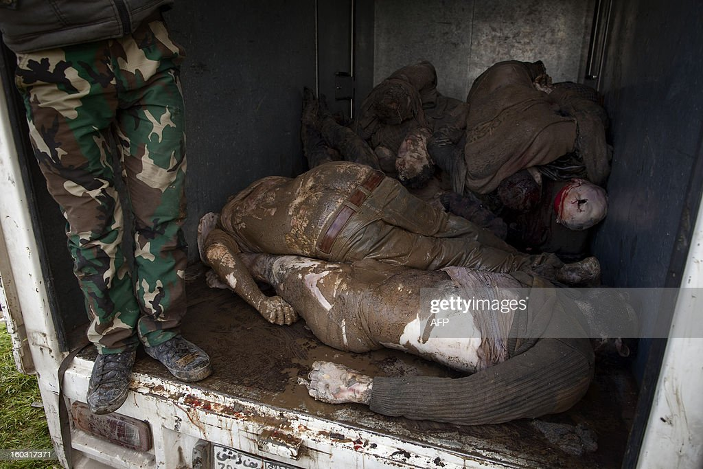 Syrian rebel stands next to the bodies of executed men being piled up in the back of a lorry in the northern city of Aleppo before transporting the corpses to a hospital where relatives could seek to identify them on January 29, 2013. The bodies of at least 68 unidentified young men and boys, all executed with a single gunshot to the head or neck, were found in the Quweiq River, which separates the Bustan al-Qasr district from Ansari in the southwest of Aleppo, in a rebel-held area where a Free Syrian Army captain said many more were still being dragged from the water.