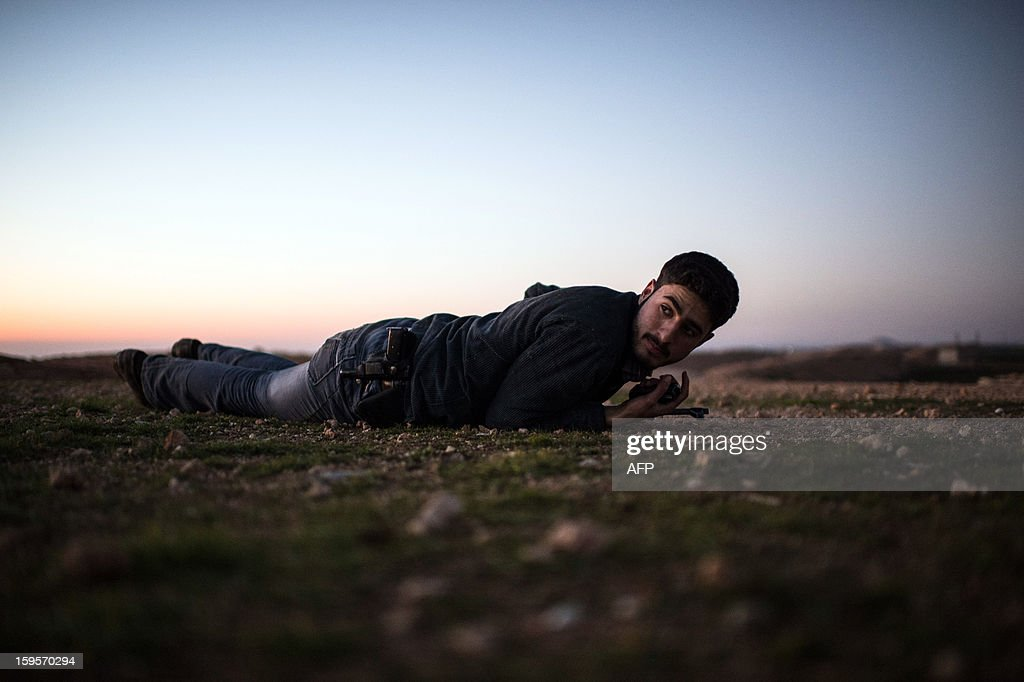 A Syrian rebel takes cover from enemy fire near the Abu Baker brigade in Albab, 30 kilometres from the northeastern Syrian city of Aleppo, on January 16, 2013. Universities were closed across Syria to mark a day of mourning called after twin blasts tore through an Aleppo campus while students were writing exams, killing at least 87 people.