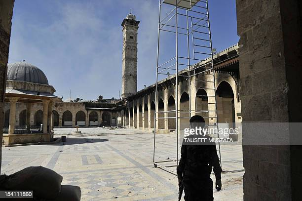 A Syrian rebel takes position at the Umayyad Mosque in the old city of Aleppo hours before the Syrian army retook control of the complex on October...