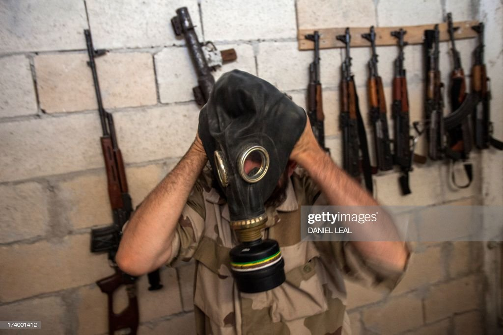 A Syrian rebel tries on a gas mask seized from a Syrian army factory in the northwestern province of Idlib on July 18, 2013. Western countries say they have handed over evidence to the UN that Bashar al-Assad's forces have used chemical arms in the two-year conflict. More than 100,000 people have died in the conflict, which morphed from a popular movement for change into an insurgency after the regime unleashed a brutal crackdown on dissent. AFP PHOTO/DANIEL LEAL-OLIVAS