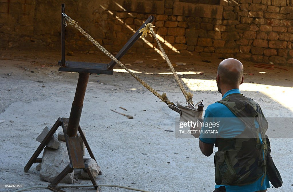 Syrian rebel uses a homemade slingshot to fire a bomb in the northern city of Aleppo on October 16, 2012. Lightly-armed Syrian rebels who face the warplanes, artillery and tanks of loyalists have turned to making their own weapons, even rigging a video game controller to fire mortar rounds.