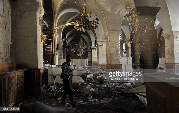 A Syrian rebel walks inside the damaged Umayyad Mosque in the old city of Aleppo hours before the Syrian army retook control of the complex on...