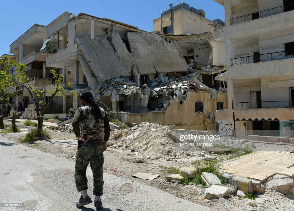 A Syrian rebel walks past a destroyed building in Salma in the coastal province of Latakia on April 26, 2013. The number of Syrians who have fled their conflict-ravaged homeland has surpassed 1.4 million, the United Nations refugee agency said, warning that it was no longer able to meet their medical needs.