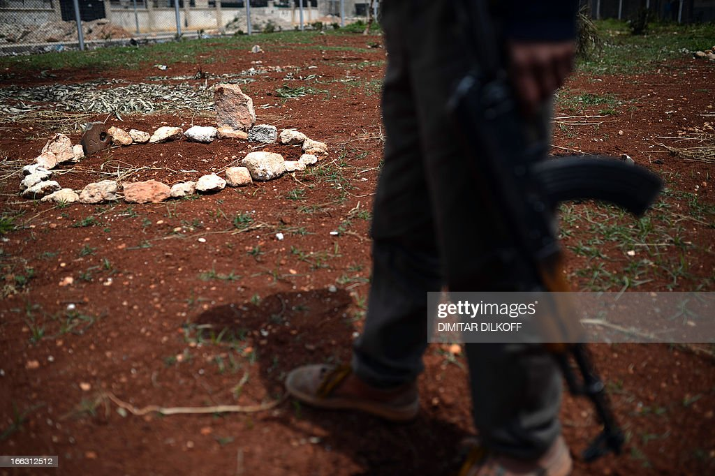 A Syrian rebel walks past a memorial of 15 people killed in an air strike earlier in the month, in the Sheikh Maqsud district of the northern Syrian city of Aleppo, on April 11, 2013. G8 foreign ministers meeting in London said they were 'appalled' by the rising death toll of more than 70,000 in the Syrian conflict and urged all countries to boost aid to a UN appeal for the country.