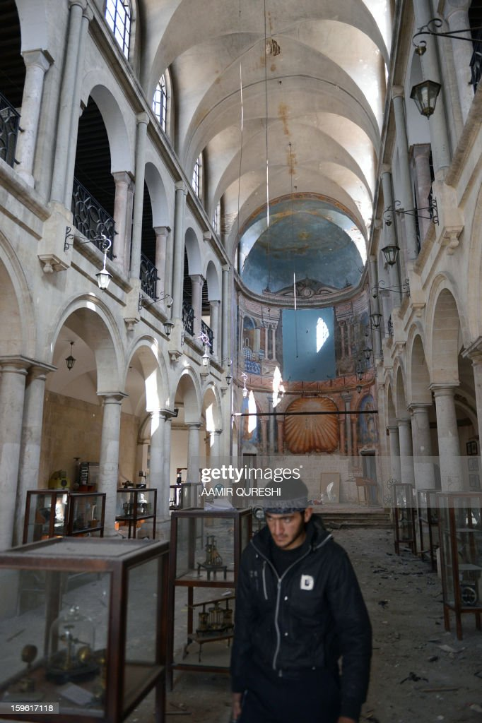 A Syrian rebel walks past damaged display cases inside a former church turned into a film museum which was shelleld by government forces in Aleppo's old city on January 17, 2013. Rebels trying to break a months-long deadlock in their battle for Syria's second city Aleppo say they are cutting supply routes ahead of simultaneous assaults on regime bases.