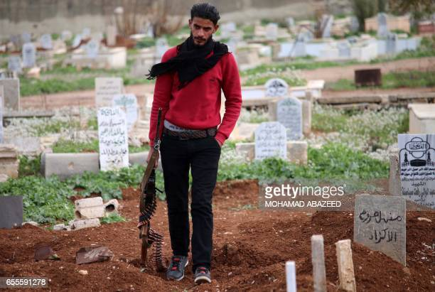 A Syrian rebel walks past graves in a cemetary in a rebelheld area in the southern city of Daraa on March 20 2017 / AFP PHOTO / MOHAMAD ABAZEED