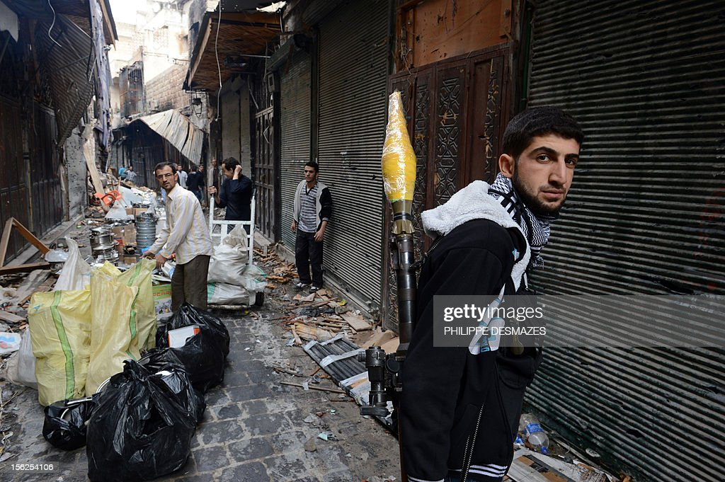 A Syrian rebel with a Rocket Propelled Grenade (RPG) stands guard next to a damaged shop in the old city of Aleppo, on November 12, 2012. Syrian troops pounded rebel lines near Damascus and in the northern city of Aleppo, while fighting raged around the northeast town of Ras al-Ain on the border with Turkey, the Syrian Observatory for Human Rights said. AFP PHOTO/PHILIPPE DESMAZES