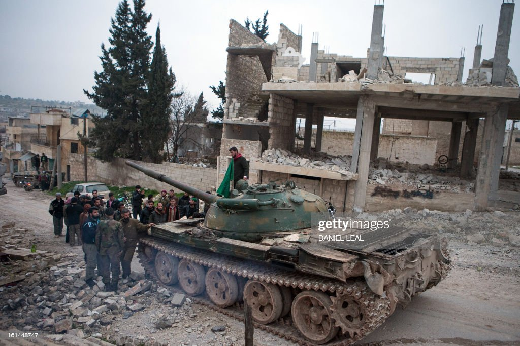 Syrian rebels gather around a T-72 tank, captured from government forces two months ago, in the village of Kfarruma in the flashpoint Syrian province of Idlib near the border with Turkey, on February 10, 2013. The rebels control large swathes of territory in northern and eastern Syria but have made little headway in major Syrian cities, where military stalemates have persisted for months. AFP PHOTO/DANIEL LEAL-OLIVAS