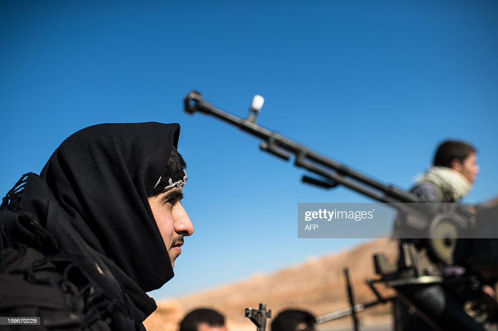 Syrian rebels gather near the Abu Baker brigade in Albab, 30 kilometres from the northeastern Syrian city of Aleppo, on January 16, 2013. Universities were closed across Syria to mark a day of mourning called after twin blasts tore through an Aleppo campus while students were writing exams, killing at least 87 people.