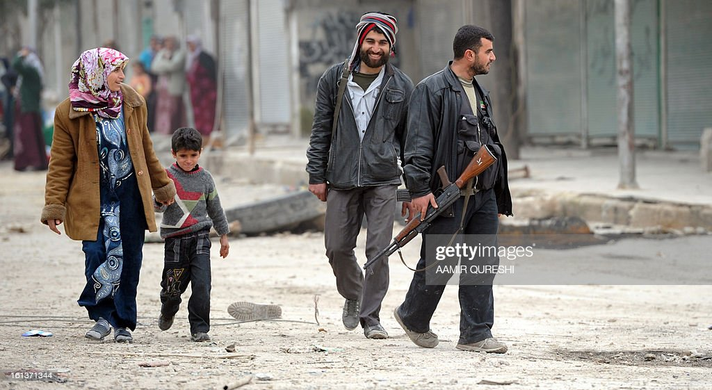 Syrian rebels help civilians cross a street during fighting with pro-regime forces in the Sheikh Said district of the northern city of Aleppo on February 10, 2013. Syrian rebels launched fierce assaults on regime troops in several parts of the country, including near Deir Ezzor where they used tanks to shell an army brigade, a watchdog and activists said. AFP PHOTO/AAMIR QURESHI