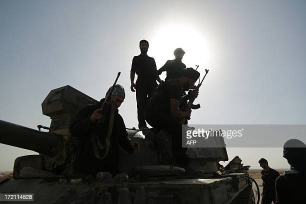 Syrian rebels inspect a tank that was left behind by government forces following clashes in the outskirts of the northern city of Raqqa on July 1...