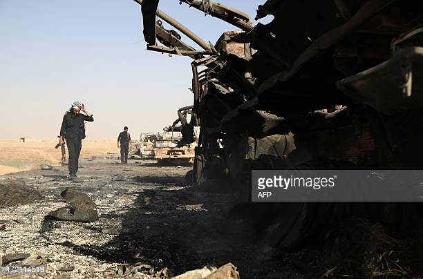 Syrian rebels inspect what's left of a convoy of government forces following clashes in the outskirts of the northern city of Raqqa on July 1 2013...