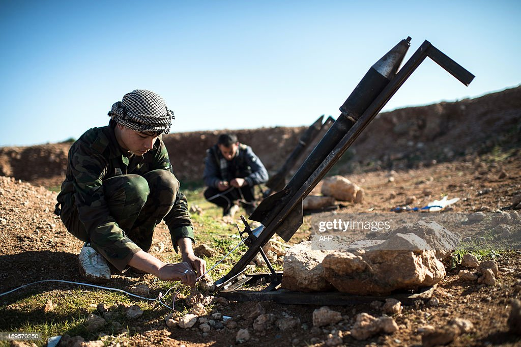 Syrian rebels prepare missiles for launch near the Abu Baker brigade in Albab, 30 kilometres from the northeastern Syrian city of Aleppo, on January 16, 2013. Universities were closed across Syria to mark a day of mourning called after twin blasts tore through an Aleppo campus while students were writing exams, killing at least 87 people. AFP PHOTO / EDOUARD ELIAS