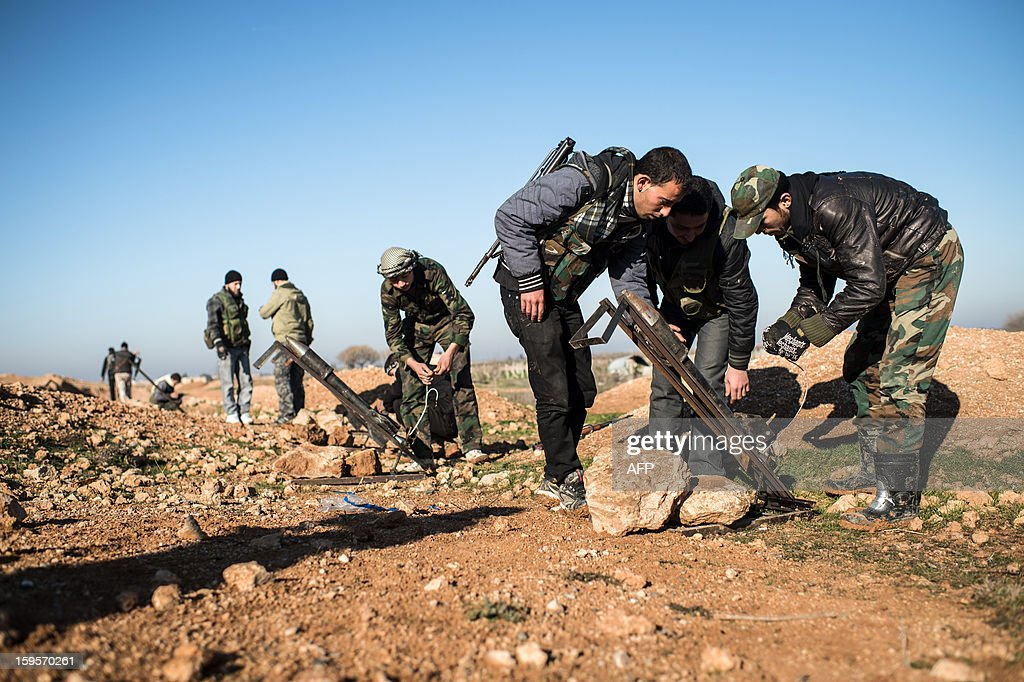 Syrian rebels prepare missiles for launch near the Abu Baker brigade in Albab, 30 kilometres from the northeastern Syrian city of Aleppo, on January 16, 2013. Universities were closed across Syria to mark a day of mourning called after twin blasts tore through an Aleppo campus while students were writing exams, killing at least 87 people.