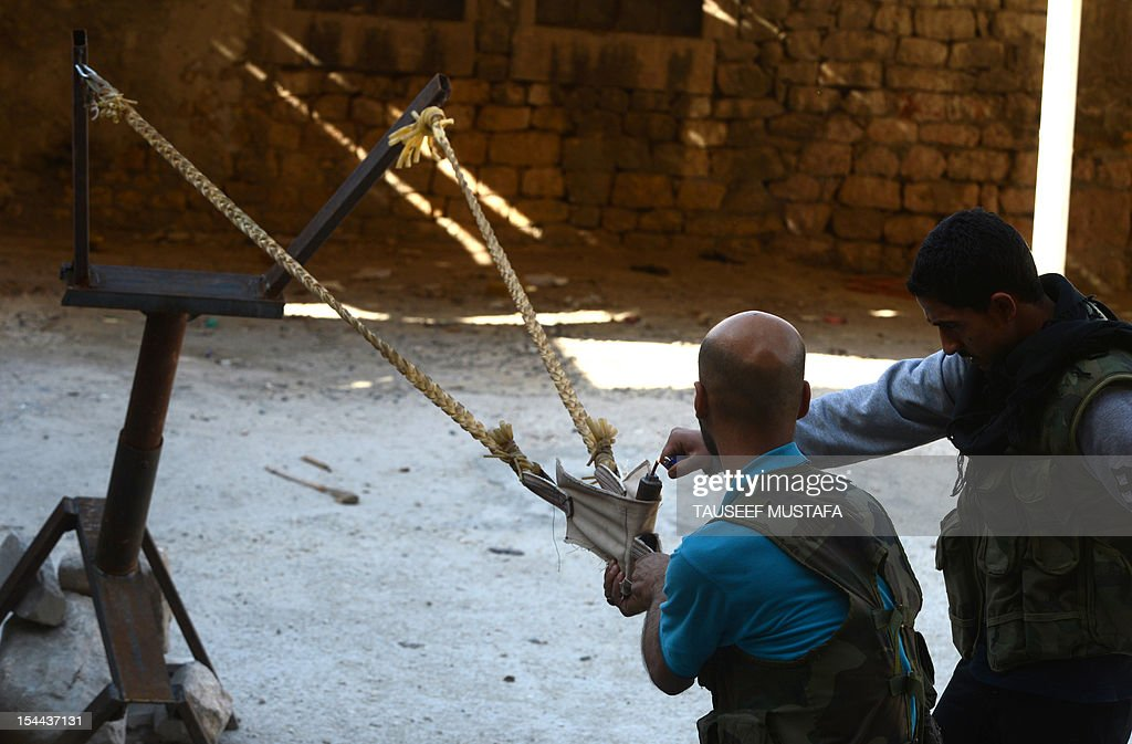 Syrian rebels prepare to fire a bomb using a homemade slingshot in the northern city of Aleppo on October 16, 2012. Lightly-armed Syrian rebels who face the warplanes, artillery and tanks of loyalists have turned to making their own weapons, even rigging a video game controller to fire mortar rounds.