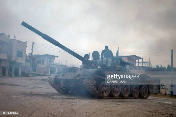 Syrian rebels relocate a T72 tank captured from government forces two months ago in the village of Kfarruma in the flashpoint Syrian province of...