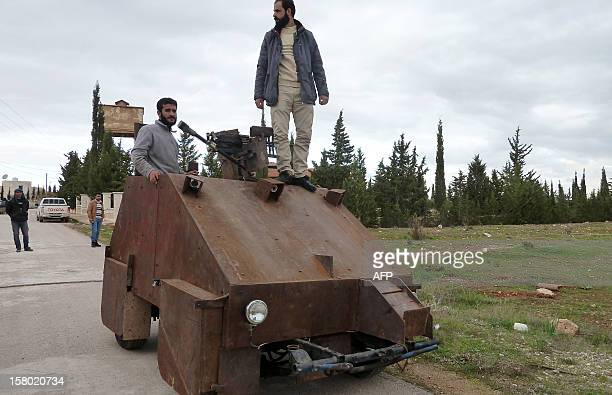 Syrian rebels stand atop Sham II a homemade armoured vehicle made by the rebels' AlAnsar brigade in Bishqatin 4 kms west of Aleppo on December 8 2012...