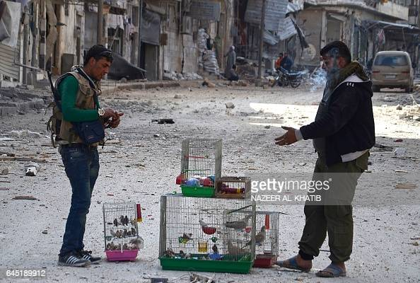 Syrian rebels take a cigarette break as they carry birds in cages in the northwestern border town of alBab on February 24 2017 after Turkishbacked...