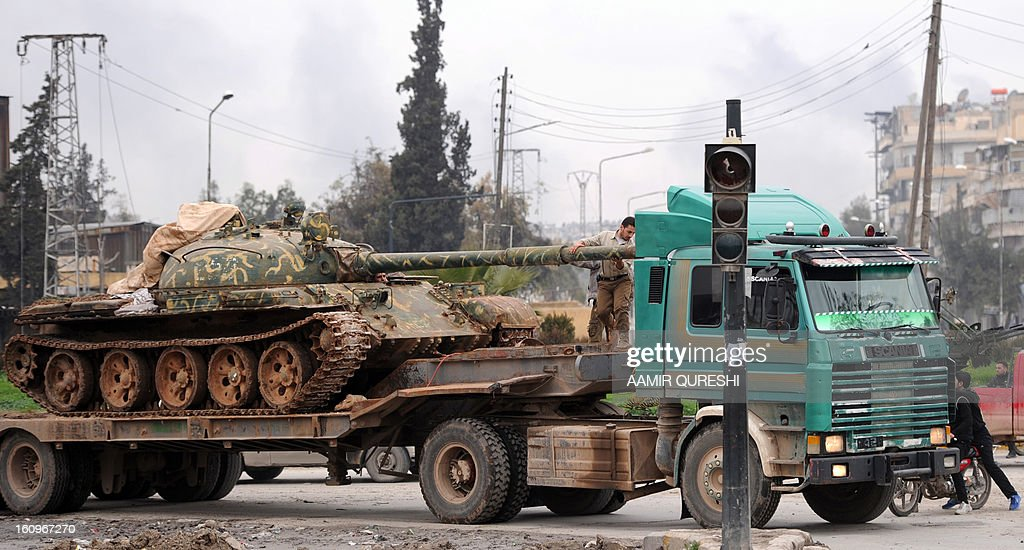 Syrian rebels transport a Soviet-made T-55 tank in the Qadi Askar district of Aleppo as they prepare to fight regime forces in the Sheikh Said district of the northern city on February 8, 2013. Syrian forces shelled rebel belts, the Syrian Observatory for Human Rights said, as an army offensive raged into a third straight day.