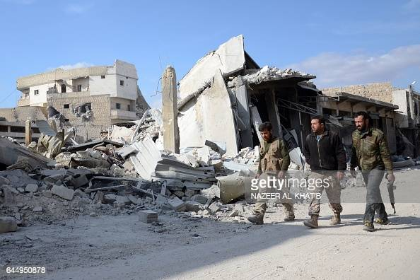Syrian rebels walk in the northwestern border town of alBab on February 24 2017 after Turkishbacked rebels announced the recapture of the town from...