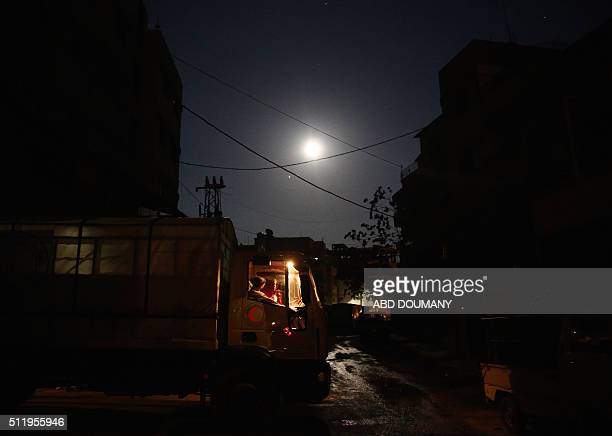 Syrian Red Crescent truck part of a convoy carrying humanitarian aid is seen under a full moon in Kafr Batna in the rebelheld Eastern Ghouta area on...