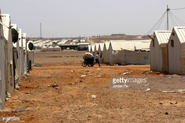Syrian refugee boy drags a cart under the hot sun near his makeshift home at the Azraq camp for Syrian refugees the newest camp in Jordan that hosts...