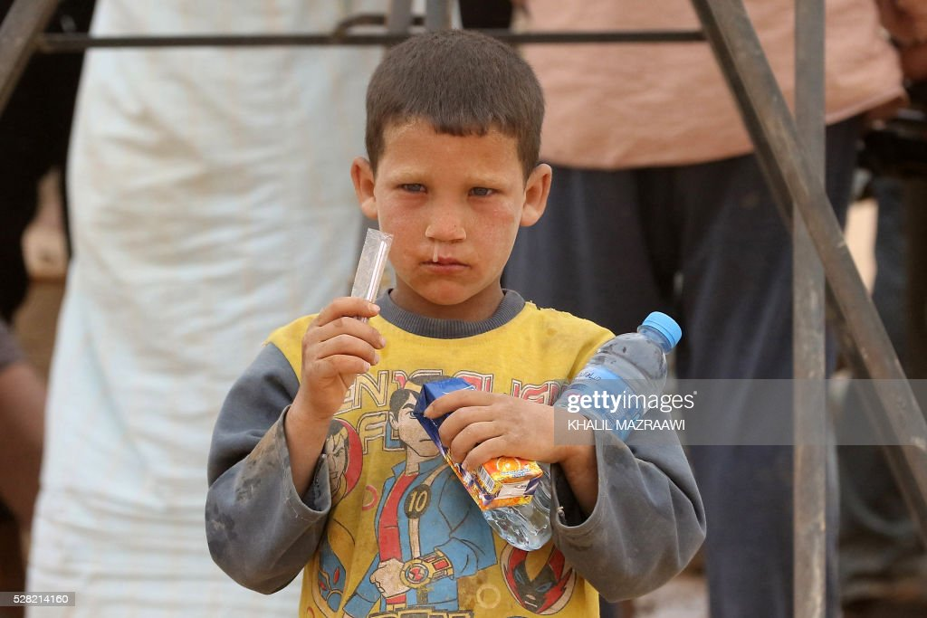 A Syrian refugee boy holds drinks distributed by the Jordanian military as he waits to cross to the Jordanian side of the Hadalat border crossing, a military zone east of the capital Amman, after arriving from Syria on May 4, 2016. According to the Jordanian Commander of the Border Guards Brigadier Saber Al-Mahayreh, around 5000 Syrians fleeing from recent attacks on the northern Syrian city of Aleppo are trying to cross into Jordan in search of safety, most of whom are exhausted and desperately in need of help and medical treatment. MAZRAAWI