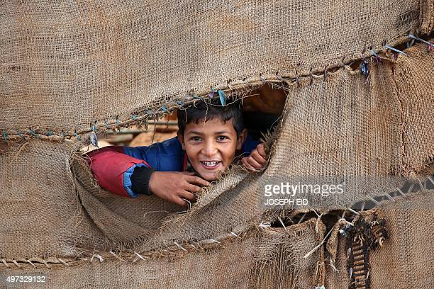 Syrian refugee boy peers through a hole on a tent on November 15 at a makeshift camp by Taybeh village in Lebanon's eastern Bekaa Valley where...