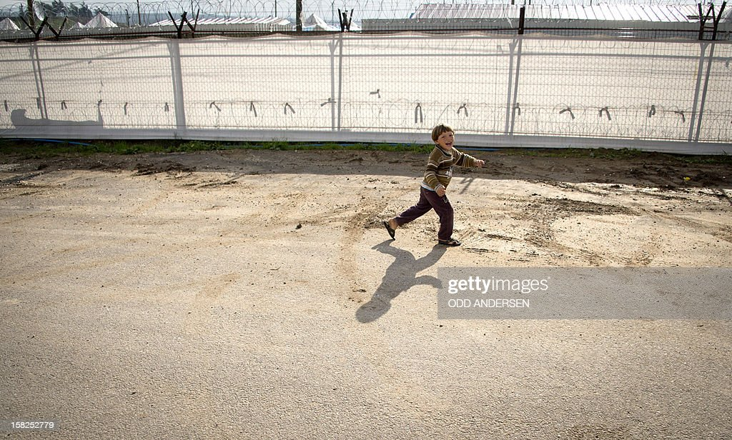A Syrian refugee boy plays along the outer fence of a refugee camp on the Syrian border near the east Turkish village of Apaydin on December 12, 2012. The number of Syrian refugees registered in neighbouring countries and North Africa has passed half a million, the UN's refugee body said on December 11, adding that many more have not come forward to seek help. The UN High Commissioner for Refugees said it had either registered or was in the process of registering 509,550 Syrians in Lebanon, Jordan, Iraq, Turkey and North Africa. AFP PHOTO / ODD ANDERSEN