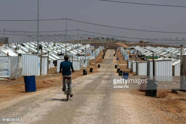 Syrian refugee boy rides his bike under the hot sun near his makeshift home at the Azraq camp for Syrian refugees the newest camp in Jordan that...