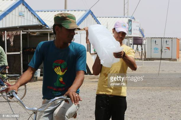 Syrian refugee boy uses his bike to transport an ice block to homeshift homes under the hot sun near his makeshift home at the Azraq camp for Syrian...