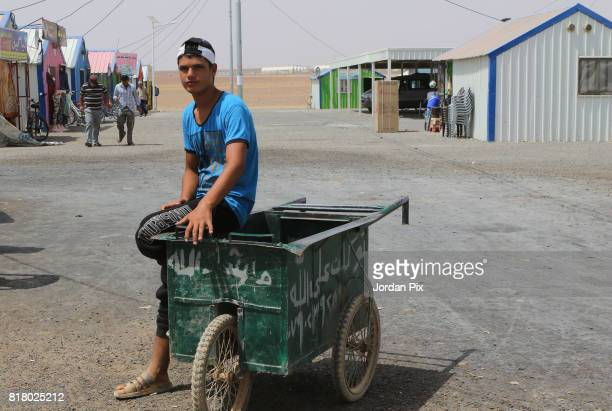 Syrian refugee boy waits with his cart at the market for clients to transport goods to their home under the hot sun near his makeshift home at the...