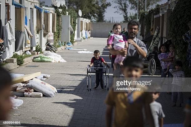 Syrian refugee boy walks past prefabricated houses at a tent city in the Akcakale District of Sanliurfa Turkey on September 24 2015 Turkish Red...