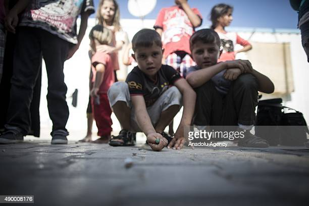 Syrian refugee boys play with marbles near their prefabricated houses at a tent city in the Harran District of Sanliurfa Turkey on September 24 2015...