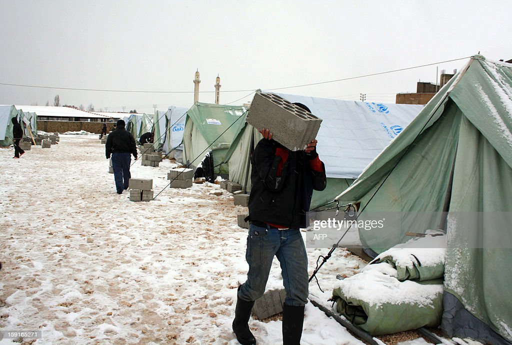 A Syrian refugee carries a breeze block to anchor down tents supplied by the United Nations High Commissioner for Refugees (UNHCR) in al-Marj, in the eastern Lebanese Bekaa Valley, on January 9, 2013, as stormy weather sparked widespread flooding, prompting chaos on the roads and a nationwide school closure. The number of Syrian refugees in Lebanon is already totaling 156,000, according to UN figures, and 200,000 according to the Lebanese government estimates.