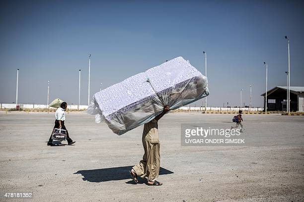 A Syrian refugee carries mattresses across the SyriaTurkey border crossing on June 22 as he returns to the northern Syrian town of Tal Abyad on the...